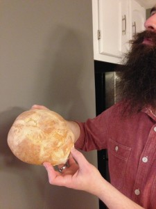 Classic Frugal Weirdo: Mr. FW holding bread he baked, next to the wall he built and the cabinets we painted, while wearing a shirt from the trash.