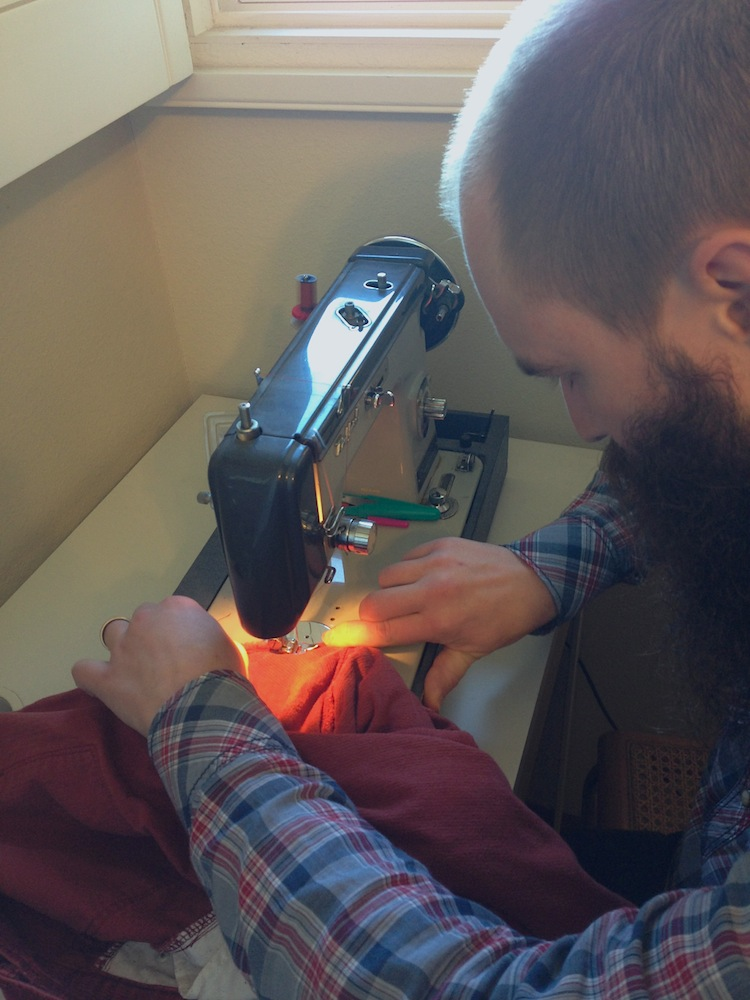 Mr. FW sewing a hole in his pants (using an iron-on patch) with my mom's sewing machine.