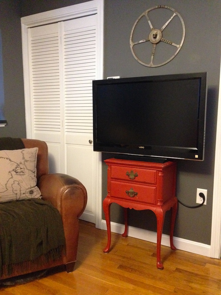 Our TV, chilling on its Craiglist stand, next to a Craigslist chair, below a Craigslist valve wheel-turned-wall-art